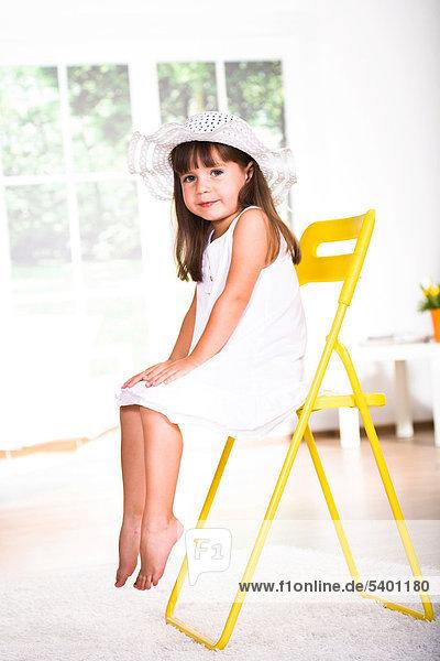 Kleines Mädchen mit weißem Kleid und Hut  auf Stuhl sitzend