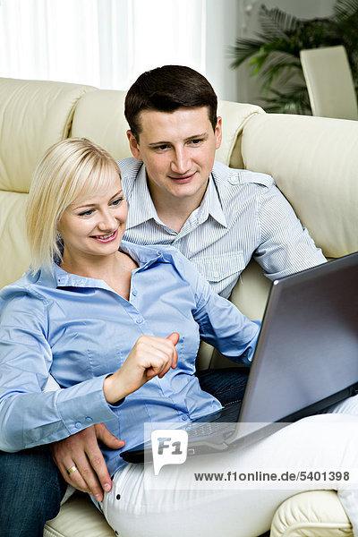 Junges Paar mit Laptop zu Hause