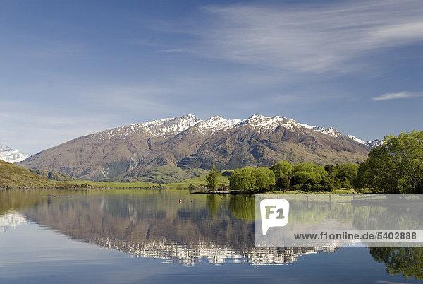 Berge der Neuseeländischen Alpen spiegeln sich im ruhigen Wasser des Sees Lake Wanaka  Südinsel  Neuseeland