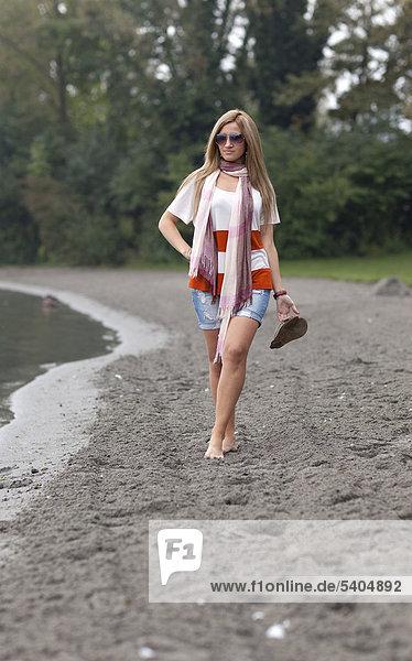 Junge blonde Frau mit Sonnenbrille und in Hotpants geht am Strand
