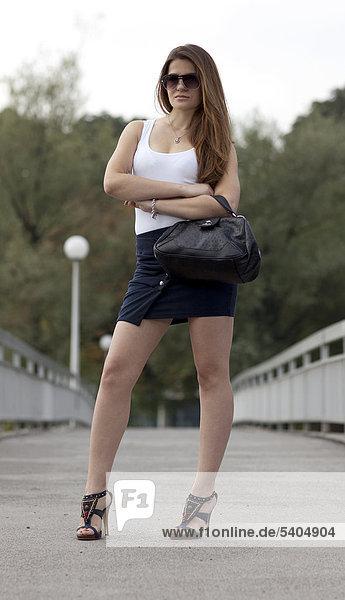 Junge Frau mit Minirock  High-Heels  Sonnenbrille und Tasche