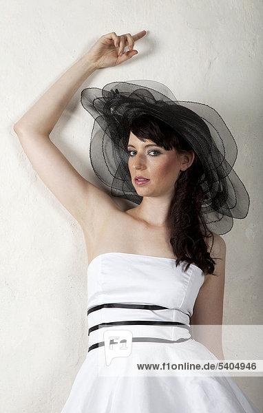 Junge Frau mit Hut und weißem Kleid