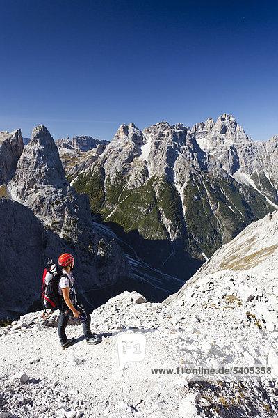 Hiker at the Strada degli Alpini via ferrata  looking towards Mt Cima Una  Mt Punta dei Tre Scarperi in the back  Val Fiscalina below  Sesto  Sexten  Alta Pusteria Valley  Dolomites  South Tyrol  Italy  Europe