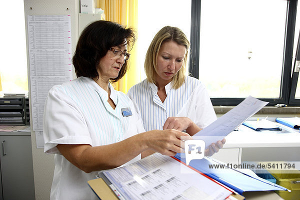 Nurses discussing the documents of patients in the nurse's station of a hospital