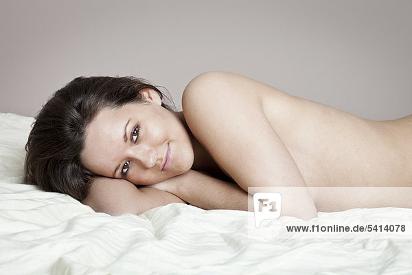 Junge Frau liegt auf einer Bettdecke