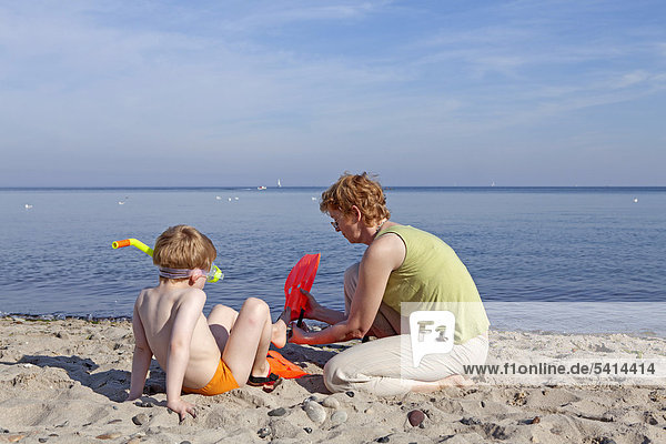 Mother helping her son put on his flippers  beach of Kuehlungsborn  Mecklenburg-Western Pomerania  Germany  Europe