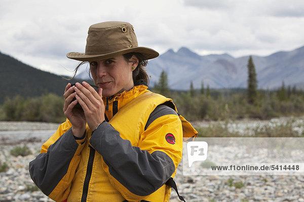 Junge Frau trinkt  genießt eine Tasse Tee  Wind River  Peel Watershed  hinten die nördlichen Mackenzie Mountains  Yukon Territory  Kanada