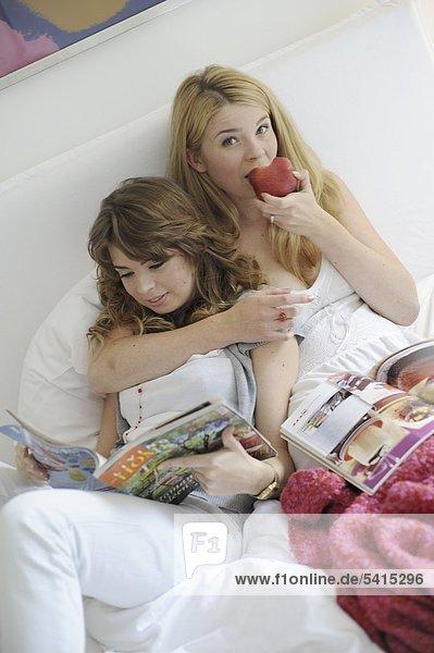 Zwei junge Frauen mit Zeitschriften und Apple im Bett