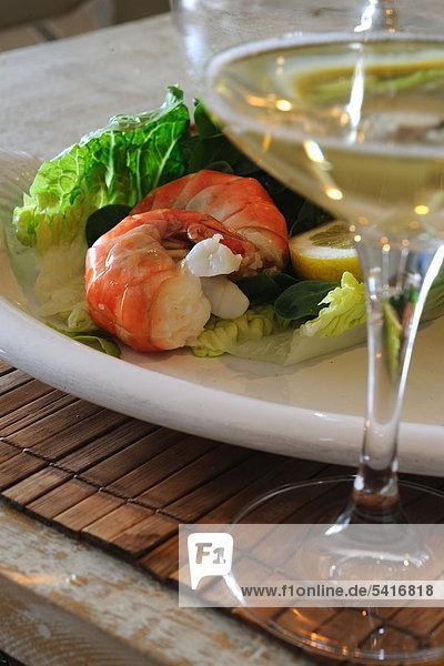 Salat mit Garnelen und Glas Weißwein