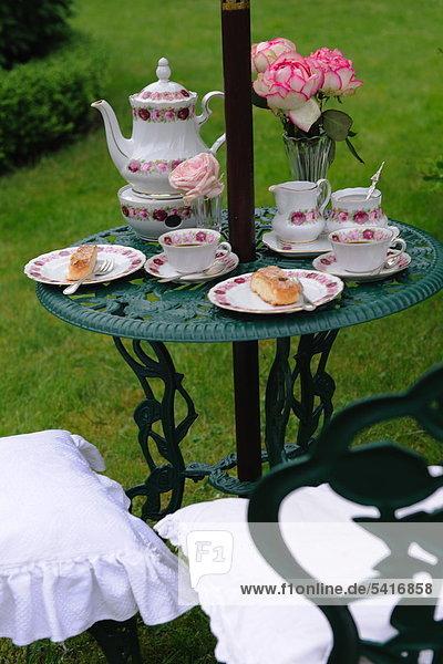 Kaffee festgelegt und Bund der Blüten am Gartentisch