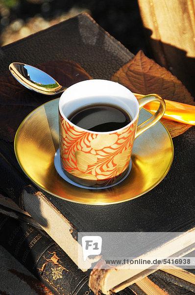 Tasse Kaffee auf Buch im freien