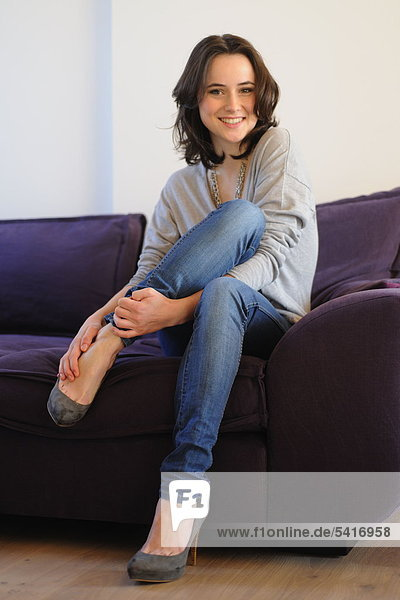 Smiling young Woman sitting on sofa
