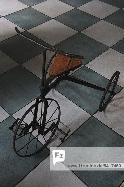 Antike Dreirad auf Fliesenboden