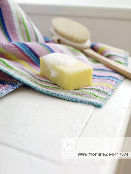Bar Rücken und Seife Brush auf gestreift Handtuch