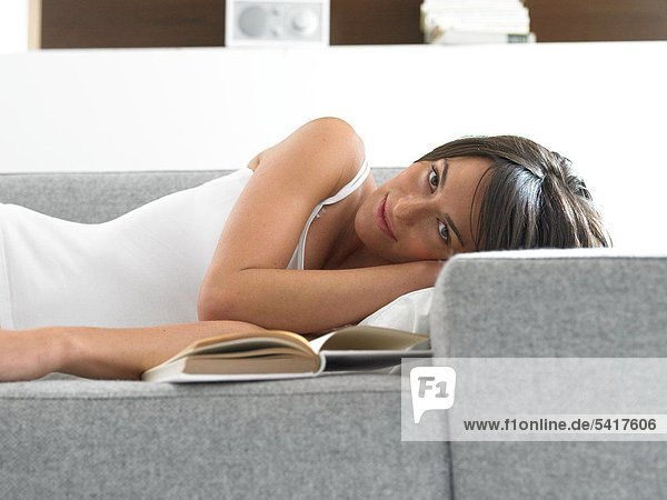 Woman lying on Couch mit Buch