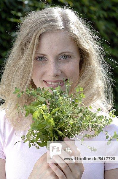 Lächelnde Frau holding Kräuter
