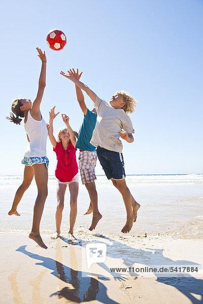 Teenager spielen Ball am Strand