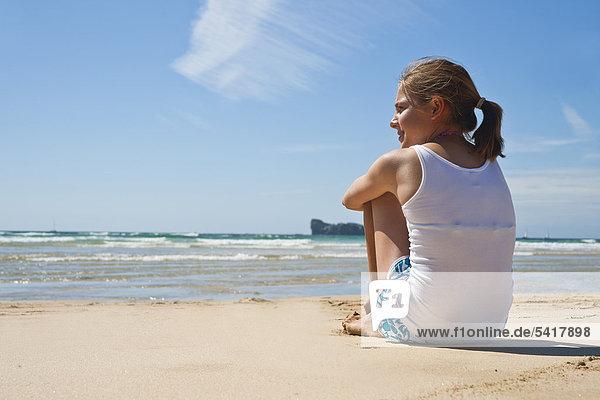 Teenagerin sitzt am Strand
