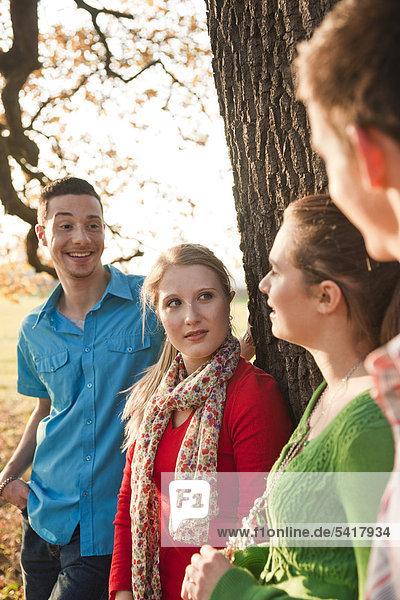 Junge Leute stehen an einem Baum