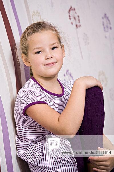 8-jähriges Mädchen sitzt mit angezogenem Bein