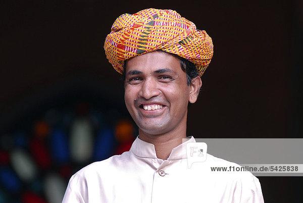 Junger Mann  Rajasthani mit buntem Turban  Porträt  Narain Niwas Hotel  Jaipur  Rajasthan  Nordindien  Asien