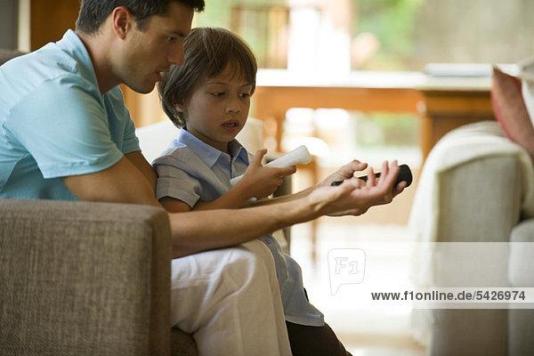 Vater und Sohn spielen Videospiel mit drahtlosen Controllern