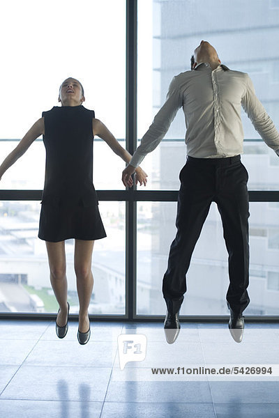 Businessman and businesswoman jumping