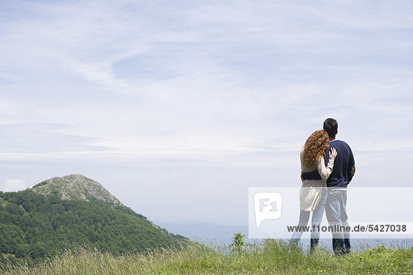 Couple enjoying scenic mountain view  rear view