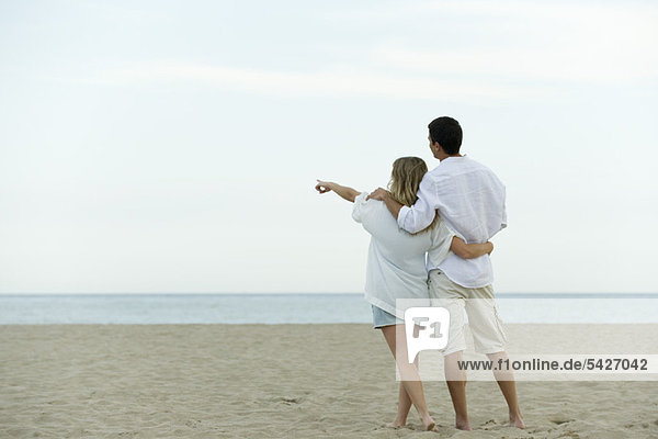 Couple walking together at the beach  woman pointing at sea