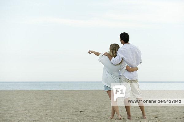 Ein Paar  das zusammen am Strand spazieren geht  eine Frau  die auf das Meer zeigt.