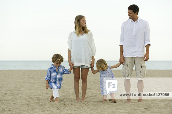 Family holding hands at the beach