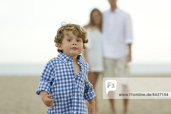 Kleiner Junge  der am Strand rennt.