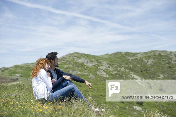 Paar auf der Wiese sitzend  Seitenansicht