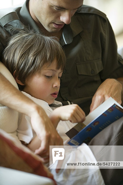Father and young son reading together  cropped