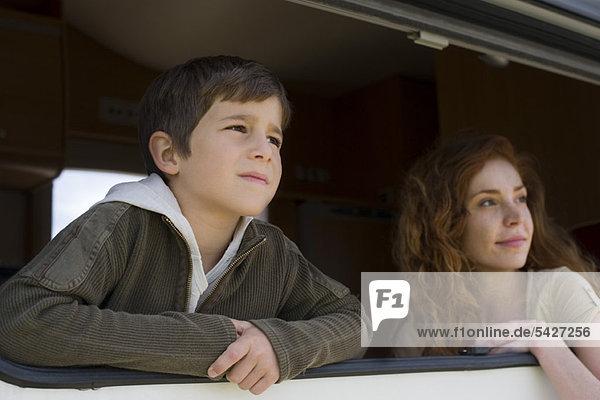 Junge und Mutter schauen aus dem Fenster des Wohnmobils.
