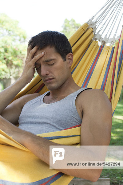 Man in hammock holding head