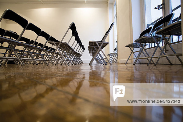 Folding chairs lined up in empty conference room