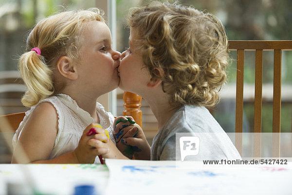 Kleine Jungen und Mädchen beim Küssen