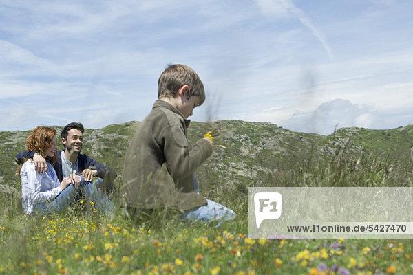 Eltern und Junge auf der Wiese sitzend