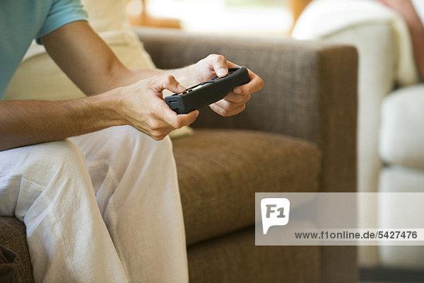 Mann spielt Videospiel mit kabelloser Steuerung  beschnitten