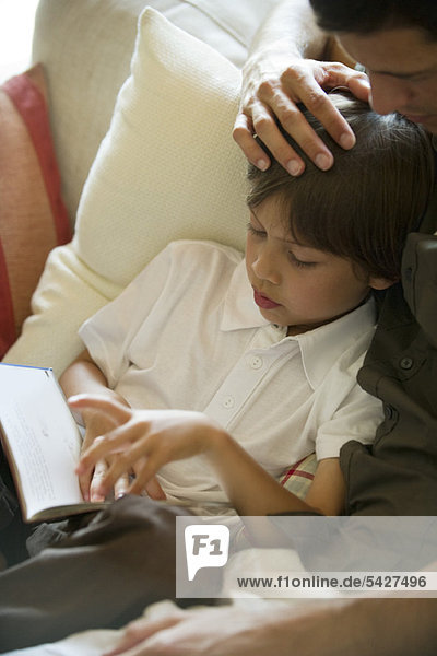 Junge liest Buch mit seinem Vater