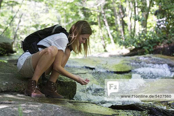 Wanderin trinkt Wasser aus dem Bach