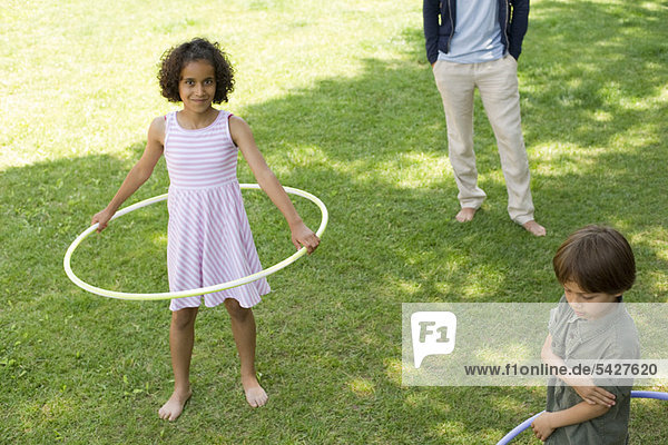 Girl playing with plastic hoop outdoors  smiling at camera