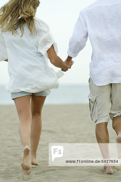 Couple running hand in hand at the beach  rear view