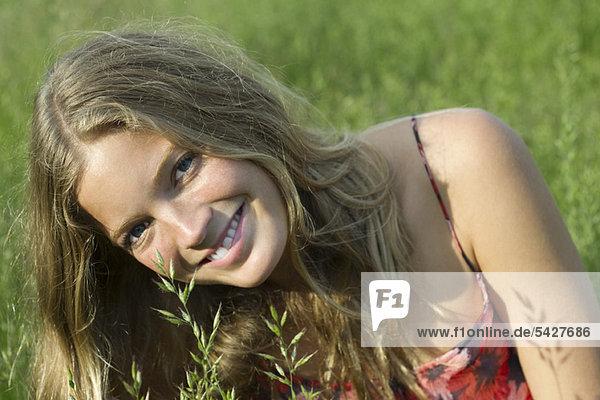 Junge Frau entspannt im hohen Gras  Portrait