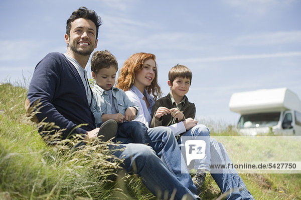 Eltern und Jungen auf der Wiese sitzend