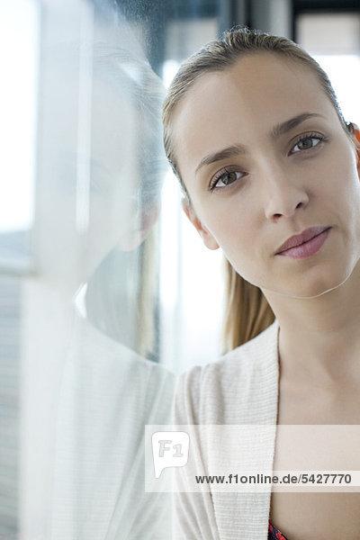 Frau lehnt sich gegen das Fenster