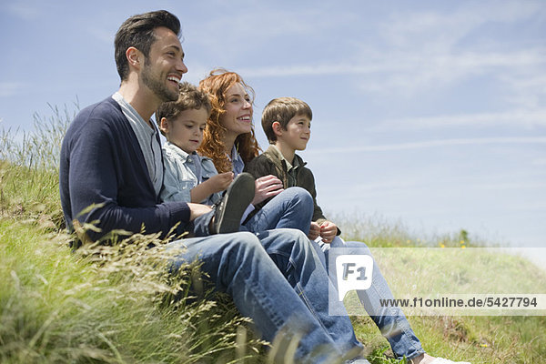 Eltern mit Jungen auf der Wiese sitzend