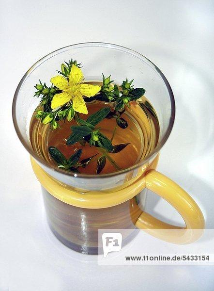Eine Glas Tee mit Johanniskraut   gelbem Henkel