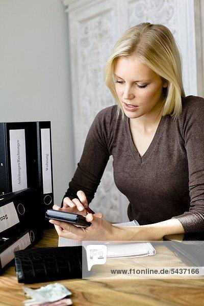 Blonde Frau benutzt einen Taschenrechner